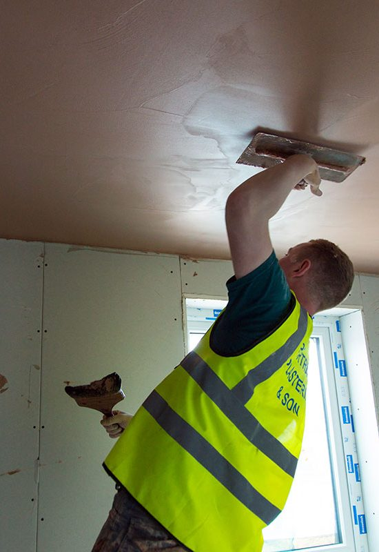 Portreath Plastering employee applying plaster to a ceiling.