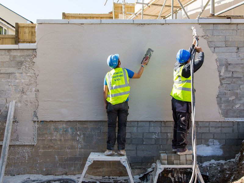 Portreath Plastering employees completing the exterior rendering of a large wall.